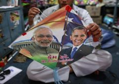 Employee ties threads on a kite, with portraits of Indian Prime Minister Narendra Modi and U.S. President Barack Obama, ahead of Obama's visit, in Mumbai