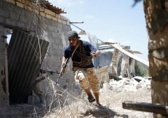 A fighter of Libyan forces allied with the U.N.-backed government runs for cover during a battle with Islamic State fighters in Sirte