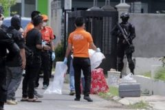 Indonesian anti-terror police and an identification team are seen outside a building during a raid in Batam