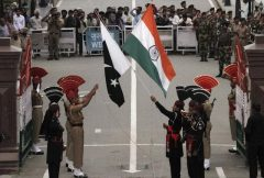 Pakistani rangers and Indian Border Security Force officers lower their national flags during a daily parade at the Pakistan-India joint check-post at Wagah