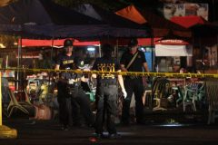 Police investigators inspect the area of a market where an explosion happened in Davao City