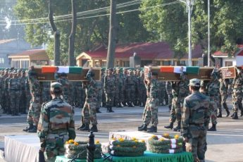 Indian army soldiers carry the coffins of their colleagues who were killed after gunmen attacked an Indian army base in Kashmir's Uri on Sunday, during a wreath laying ceremony in Srinagar