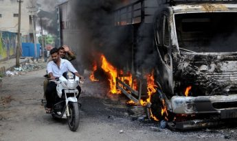 Men ride a motorcycle past a lorry in Bengaluru, which was set on fire by protesters after India's Supreme Court ordered Karnataka state to release 12,000 cubic feet of water per second every day from the Cauvery river to neighboring Tamil Nadu, India September 12, 2016. REUTERS/Abhishek N. Chinnappa