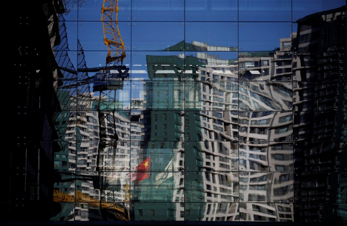 A construction site and a residential building are reflected on the glass wall of a building in Beijing. REUTERS/Kim Kyung-Hoon