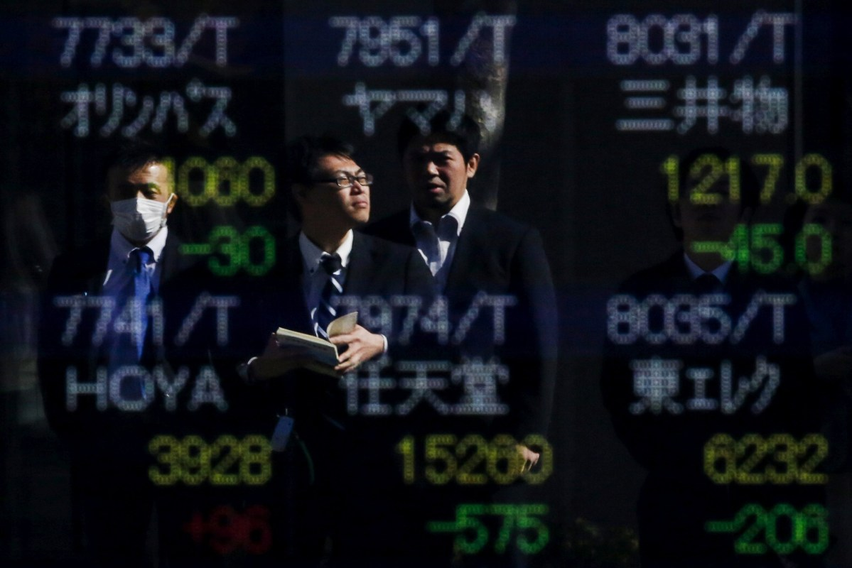 People are reflected in a display showing market indices outside a brokerage in Tokyo, Japan. REUTERS/Thomas Peter/File Photo