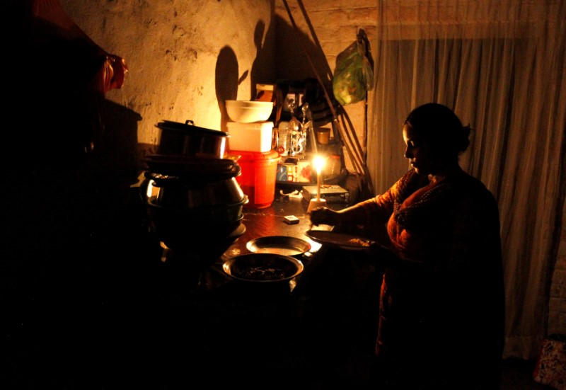 A woman cleans up after dinner in her home during a power cut in Islamabad, Pakistan October 8,  2016. REUTERS/Caren Firouz