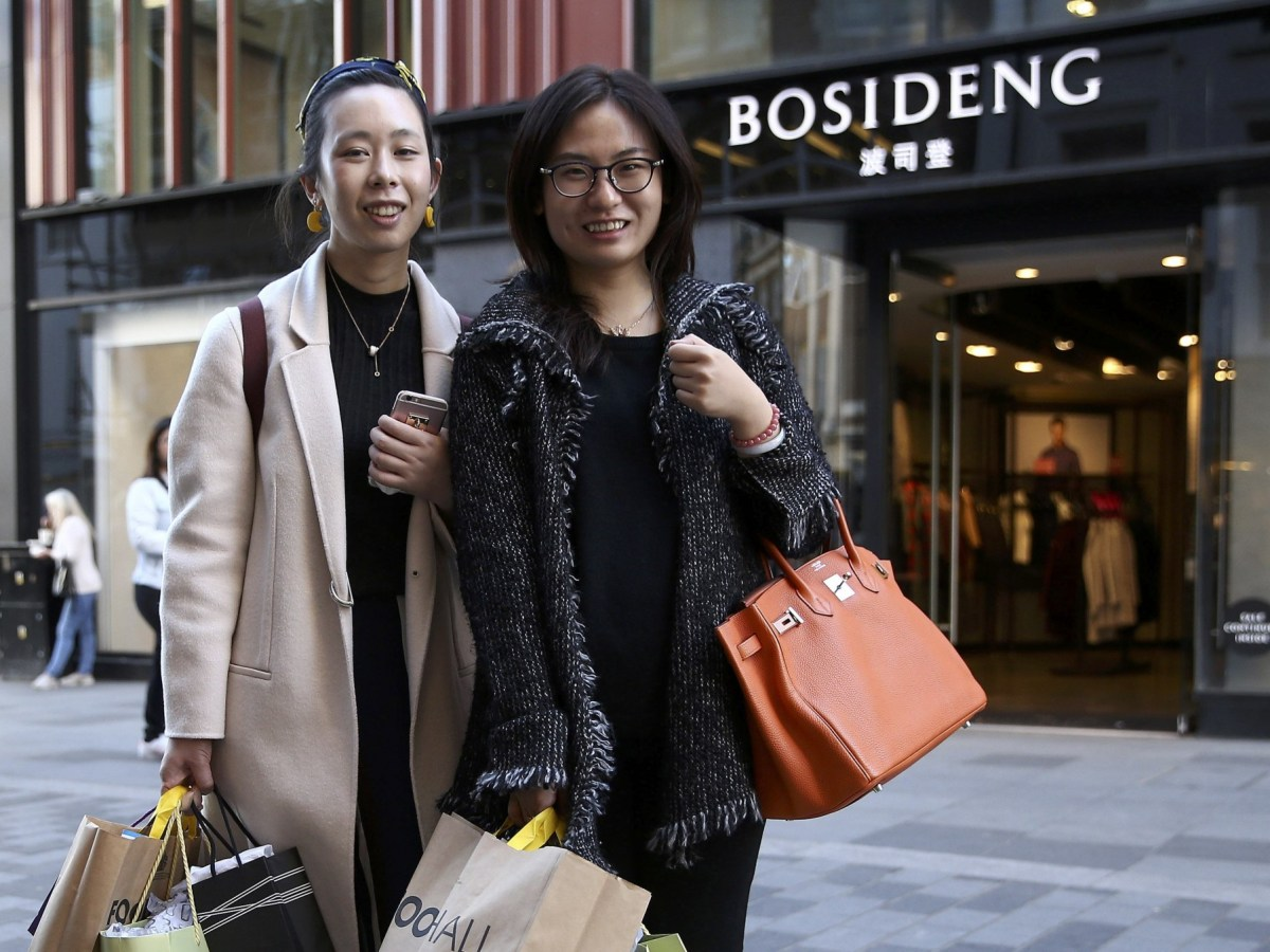 Chinese tourists Haiti Chen (left) and Jialin Wang brandish shopping bags in Central London, October 5, 2016. Photo: Reuters/Neil Hall