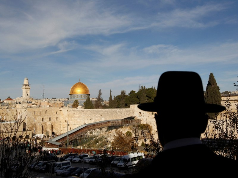 An ultra-Orthodox Jewish man overlooks Judaism's Western Wall and the sacred compound known to Muslims as the Noble Sanctuary and to Jews as Temple Mount, where the al-Aqsa mosque and the Dome of the Rock shrine stand in Jerusalem. Photo: REUTERS/Ronen Zvulun