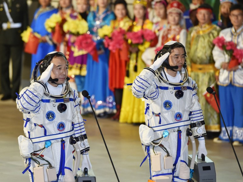 Chinese astronauts Jing Haipeng (L), Chen Dong salute before the launch of Shenzhou-11 spacecraft, in Jiuquan, China on October 17, 2016. China Daily/via Reuters