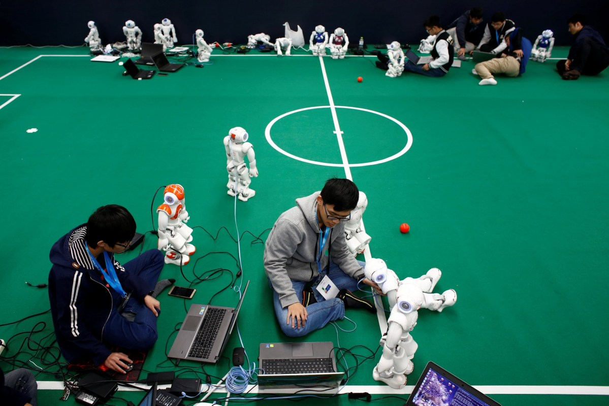 Remember, lads, we're going to play in a binary formation. Programers ready their robots for a robot soccer match at the World Robot Conference 2016 in Beijing, China. Photo: Reuters/Thomas Peter
