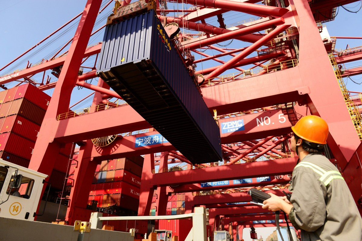 A worker looks at a container box being lifted at a port in Ningbo. Photo: Reuters