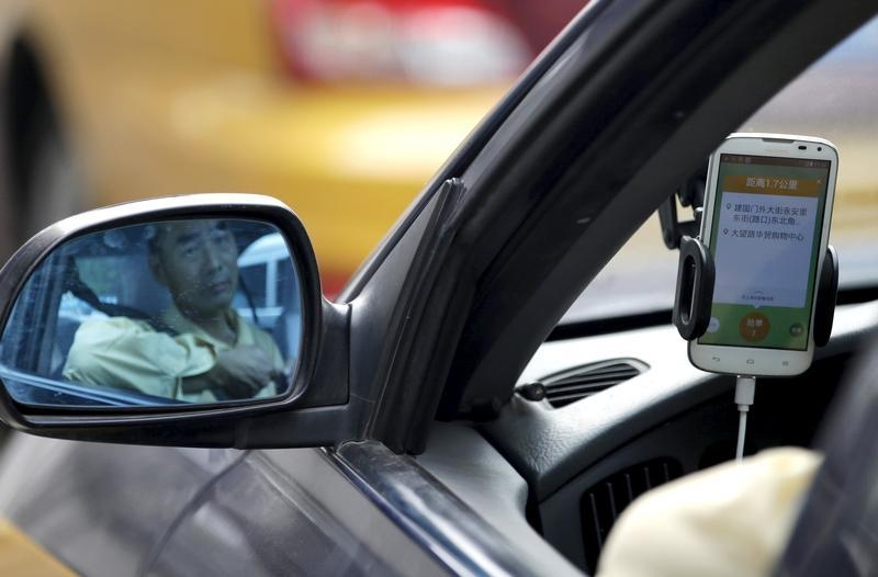 A taxi driver is reflected in a side mirror as he uses the Didi Chuxing car-hailing application in Beijing, China. Photo: Reuters/Jason Lee