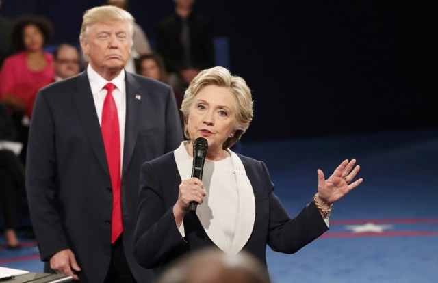 Republican presidential nominee Donald Trump listens as Democratic nominee Hillary Clinton answers a question during a debate in October. Photo: Reuters, Rick Wilking