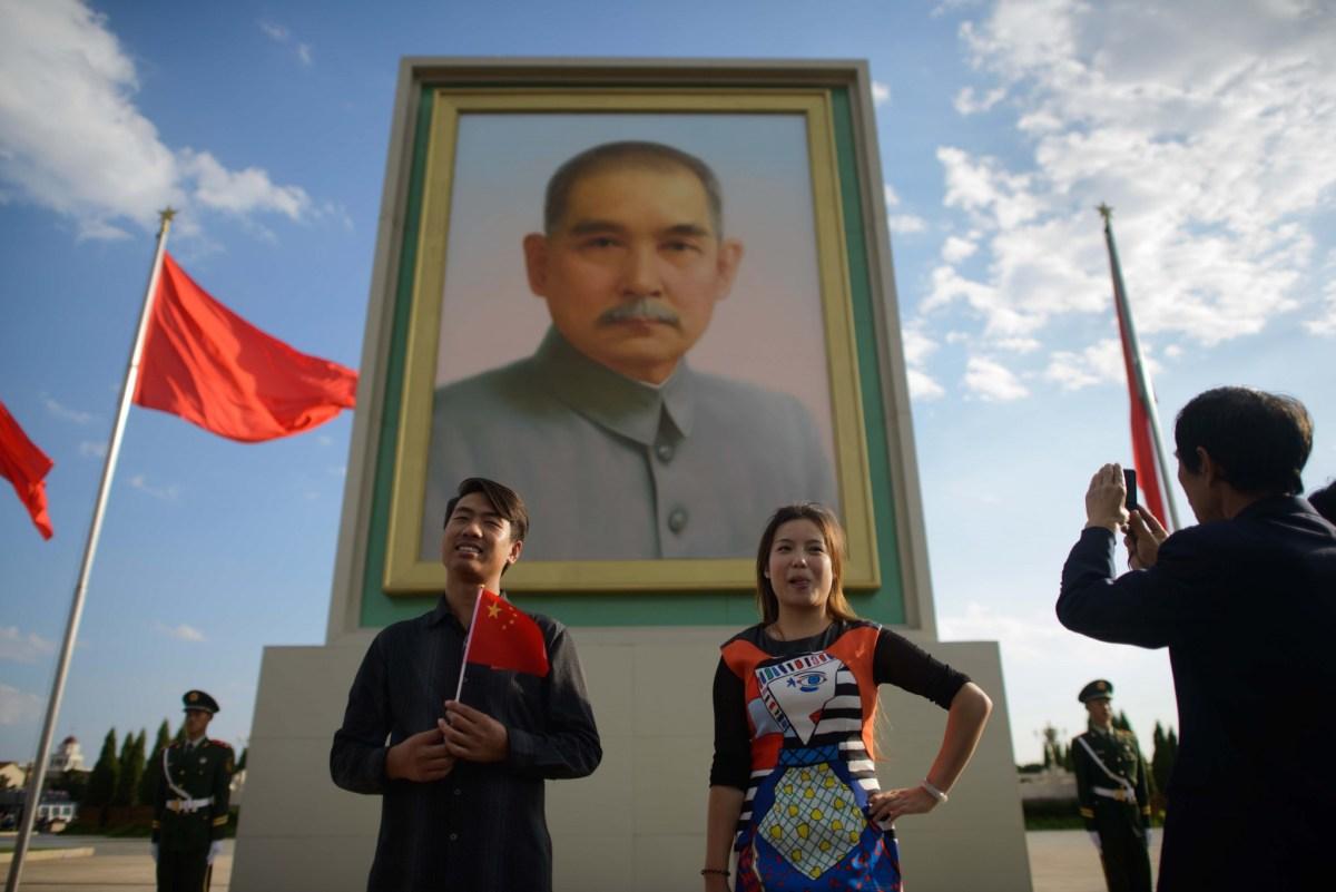 Tourists pose before a portrait of Dr. Sun Yat-sen in Tiananmen Square in Beijing. Photo: AFP PHOTO / Ed Jones