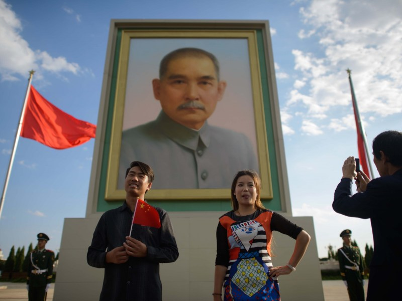 Tourists pose before a portrait of Dr. Sun Yat-sen in Tiananmen Square in Beijing. Photo: AFP PHOTO / Ed Jones