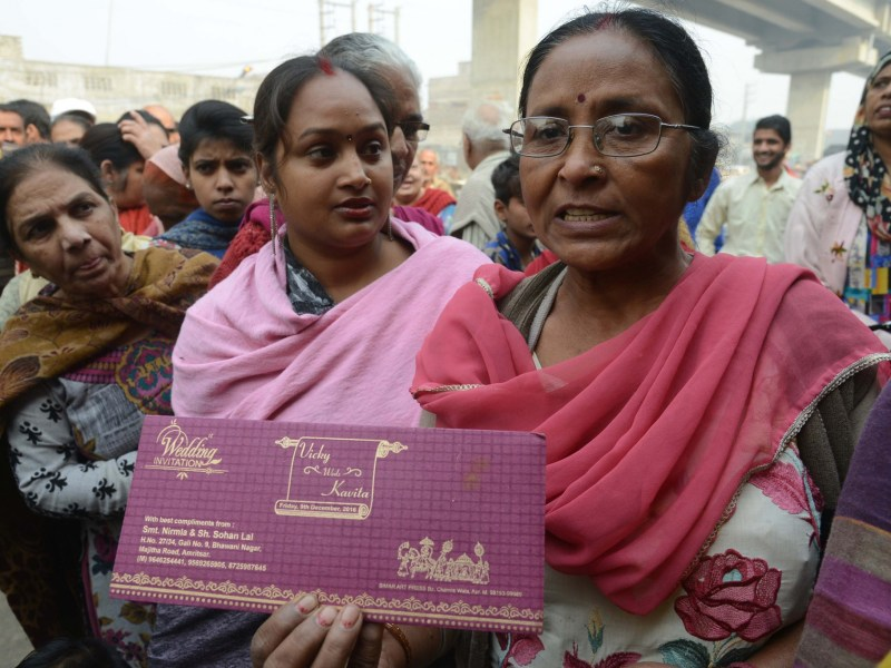 An Indian mother in a bank queue holds her son's wedding invitation card, in the hopes of withdrawing money for the event. Photo: AFP/Narinder Nanu
