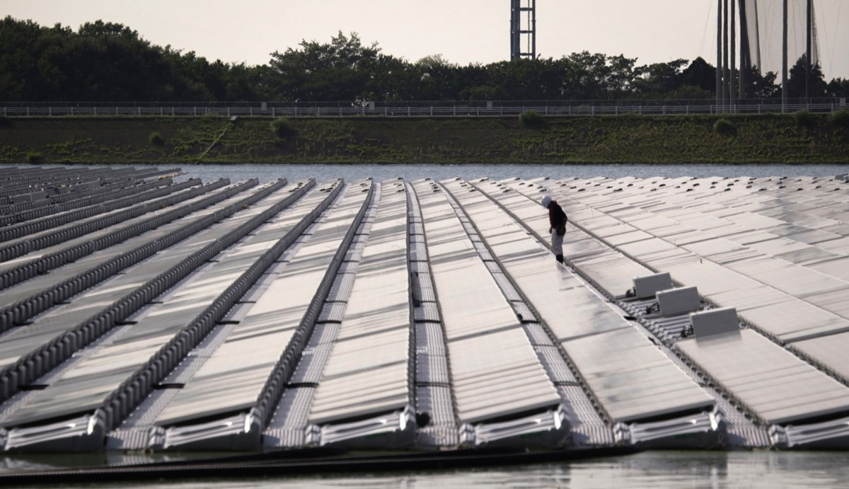 A Japanese worker checks solar panels at a floating solar farm on the Yamakura dam reservoir near Ichihara city in Chiba prefecture. Photo: AFP/ Quentin Tyberghien