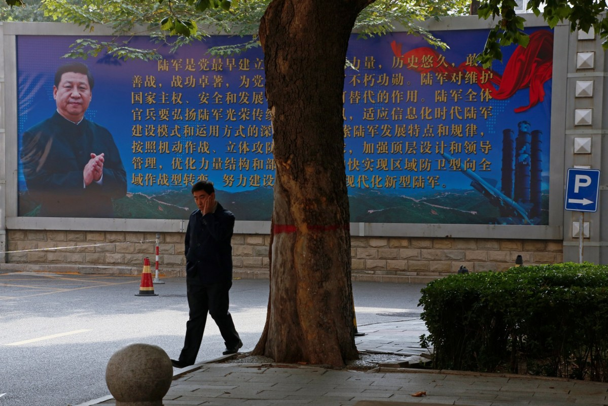 A man walks past a poster about the People's Liberation Army featuring a portrait of President Xi Jinping. Photo: Reuters / Thomas Peter