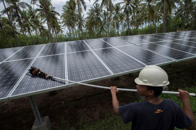 An employee of PT Perusahaan Listrik Negara (PLN) cleans the surface of solar panels at a solar power generation plant in Gili Meno island, in this December 9, 2014 photo taken by Antara Foto. Photo: Reuters/Antara Foto/Widodo S. Jusuf