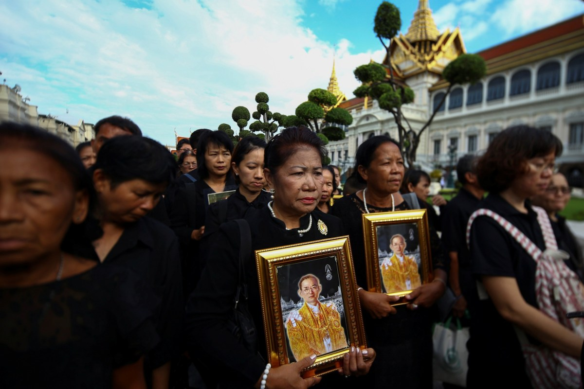 Mourners hold up pictures of Thailand's late King Bhumibol Adulayadej. Photo: Reuters, Athit Perawongmetha