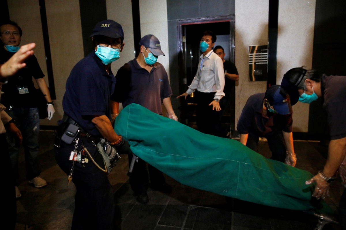 Government workers remove the body of one of the murder victims found at British banker Rurik Jutting's residential flat in Hong Kong on November 1, 2014. Photo: Reuters/Tyrone Siu