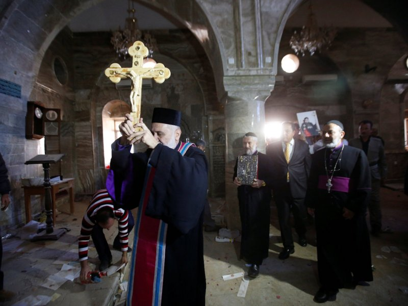 Iraqi Christians take part in a procession to erect a new cross over the Mar Korkeis church, after the original cross was destroyed by Islamic State militants, in the town of Bashiqa, Iraq, November 19, 2016. Photo: Reuters/Azad Lashkari