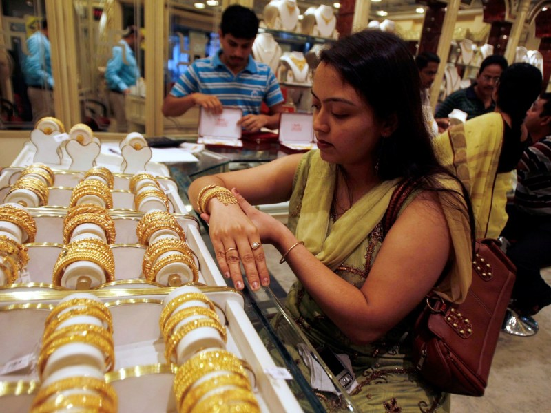 A woman tries on a gold bracelet at a jewelery showroom in the eastern Indian city of Siliguri. Photo: Reuters/Rupak De Chowdhuri