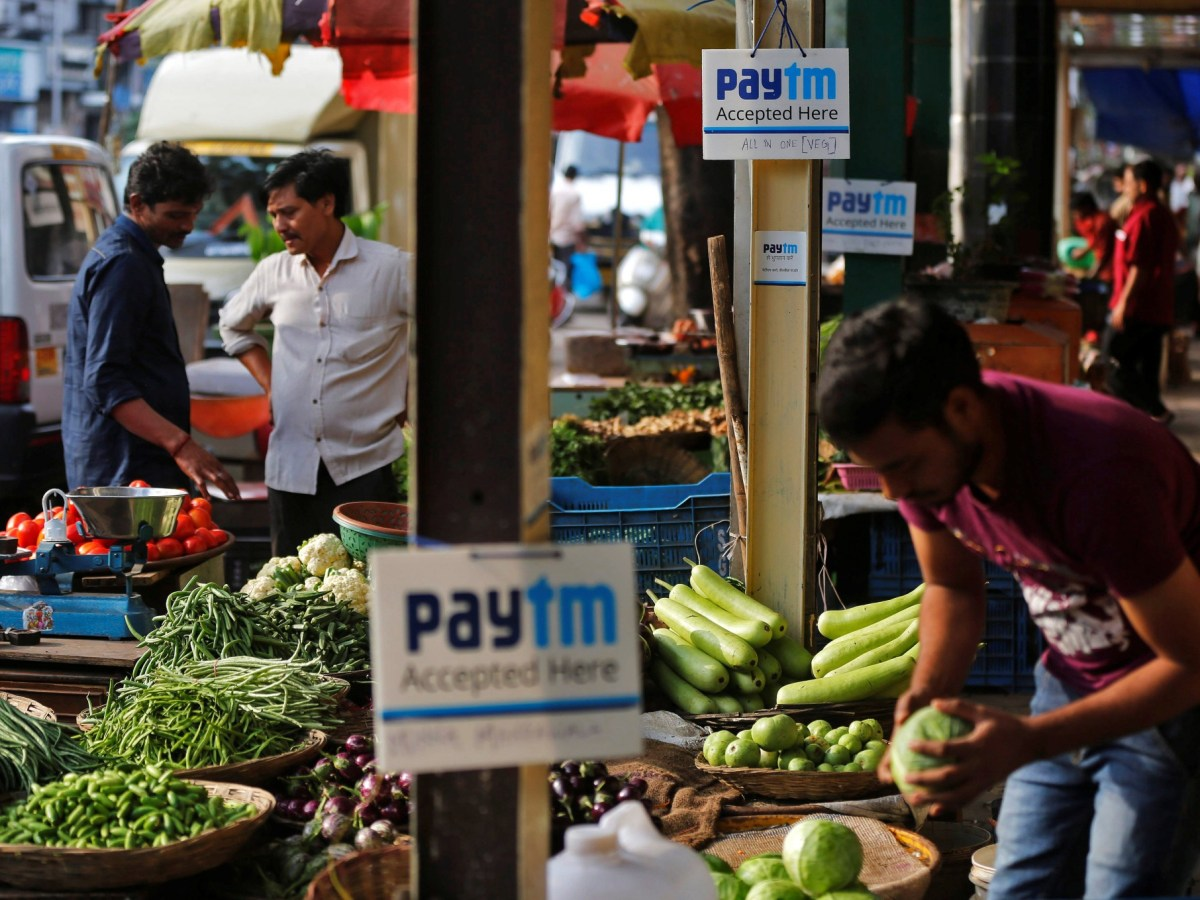 Advertising boards for Paytm, a digital payment company, are seen at stalls of roadside vegetable vendors as they wait for customers in Mumbai. Photo: Reuters