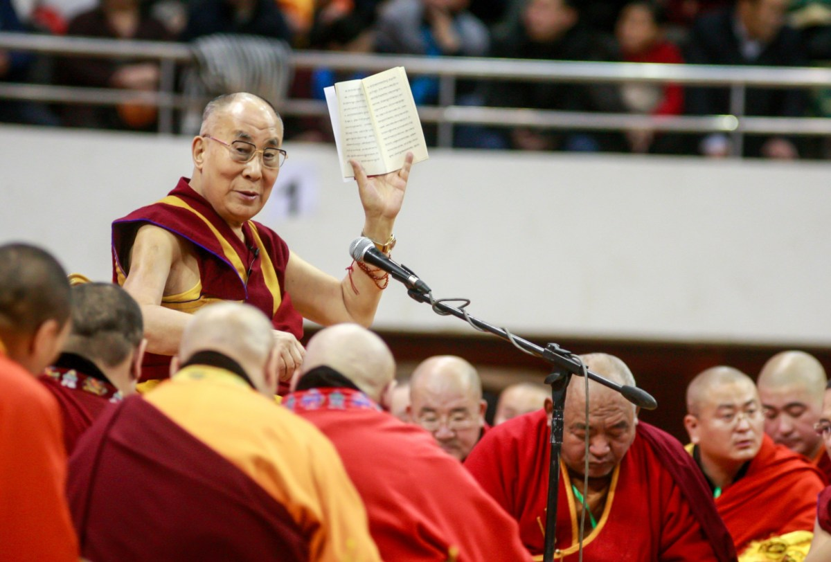 The Dalai Lama waves to worshippers during ceremonies at the Buyant Ukhaa sports stadium in Ulan Bator. Photo: AFP/ Byambasuren Byamba-Ochir