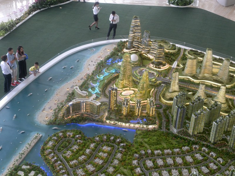 Prospective property buyers  view the scale model of development at Forest City on one of the man-made islands on the Malaysian side of the Straits of Johor. Photo: AFP/Roslan Rahman