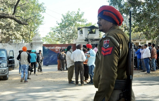 An Indian police personnel and people stand in front of Nabha prison in Punjab after the jailbreak on Sunday -- Photo/AFP