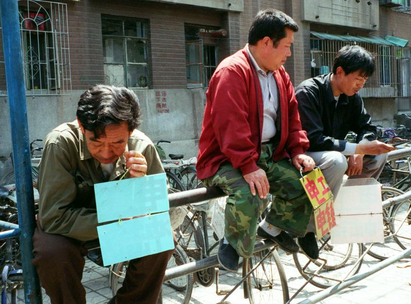 Jobless workers holding placards advertising their skills wait for work in a street in Shenyang, capital of the rustbelt province of Liaoning. Photo: Reuters