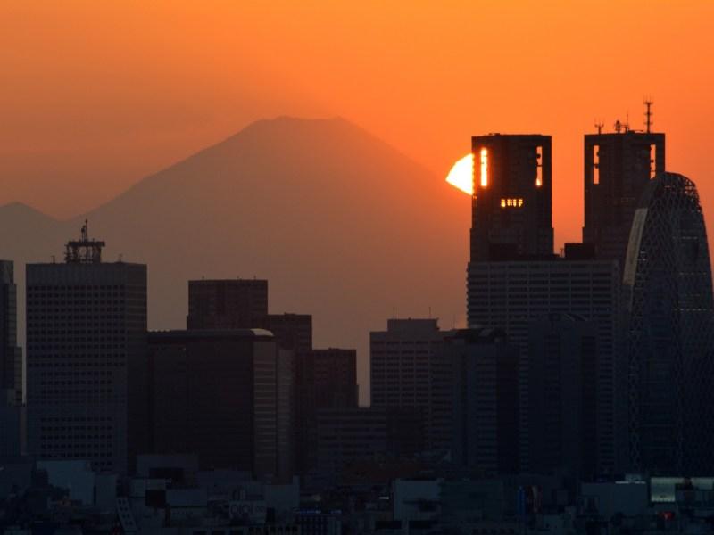 The sun sets behind Mount Fuji and skyscrapers in Tokyo's Shinjuku area. Photo: Kazuhiro Nogi/AFP