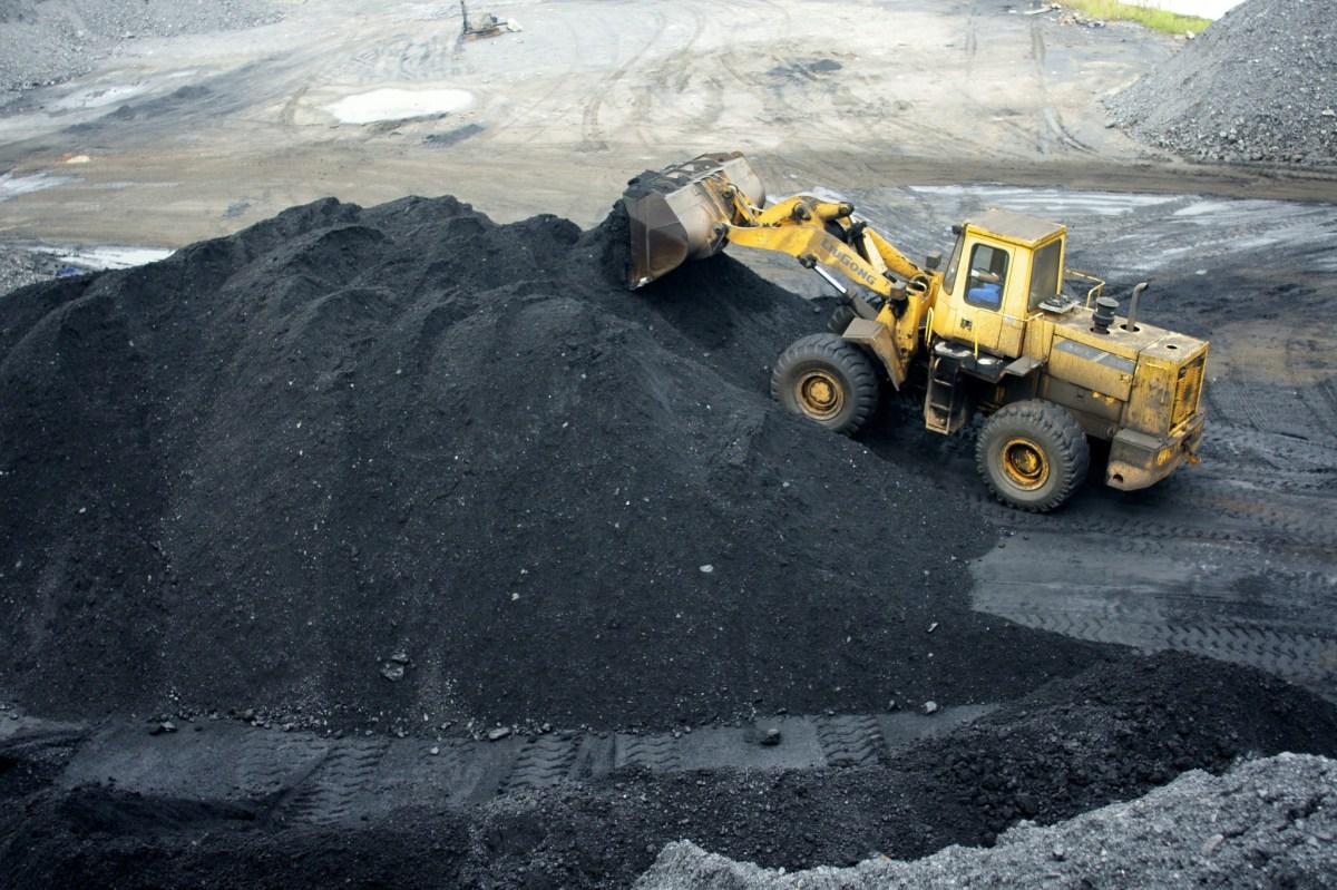 A wheel loader piles up coal at a coalyard in Yichang city, central China's Hubei province. Photo: AFP, Zhou jianping/Imaginechina