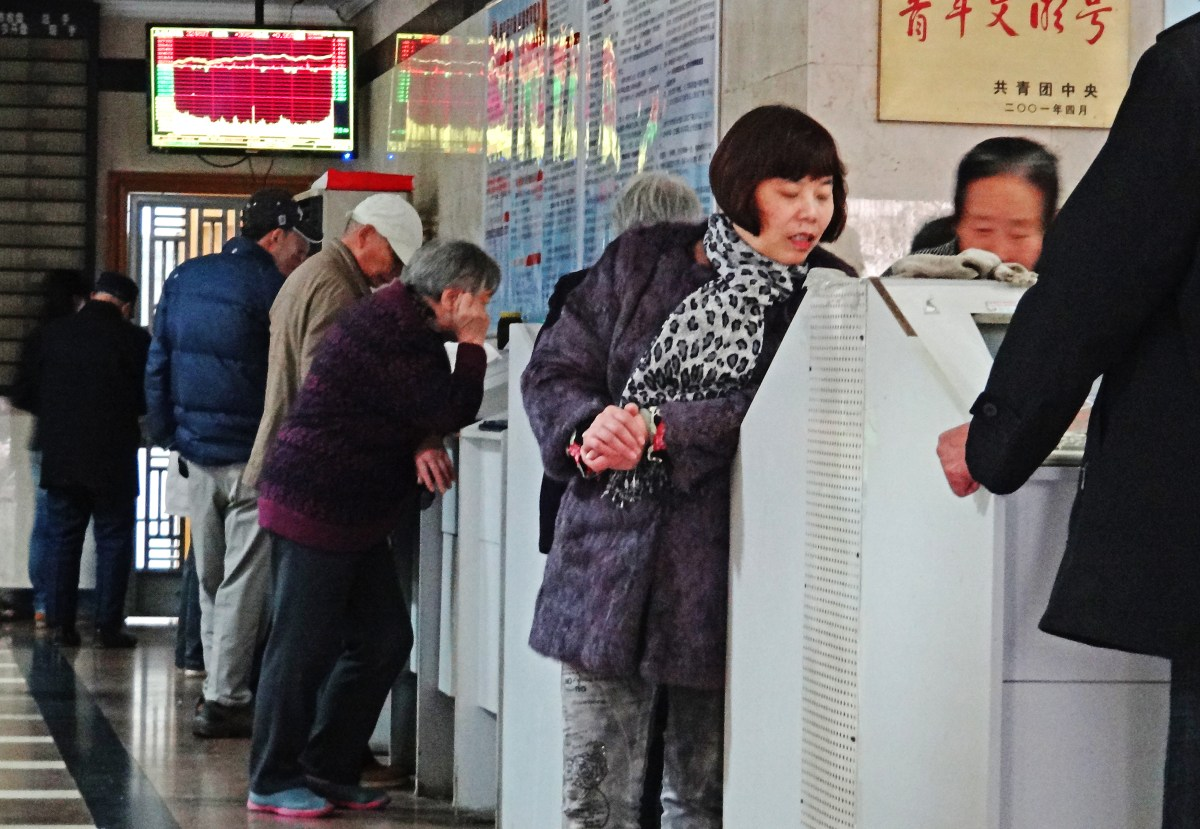 Chinese investors check out prices at a brokerage house in Nanjing city, east China's Jiangsu province. Photo: AFP