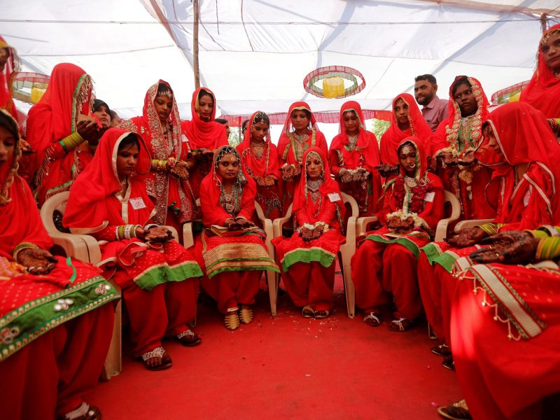 Brides sit and wait for their turn during a Muslim mass wedding. Photo: Reuters/Amit Dave
