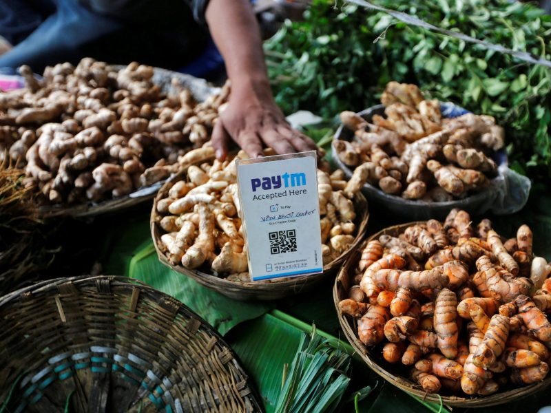 An advertisement board displaying a QR code for Paytm, a digital wallet company, is seen placed amidst vegetables at a roadside vendor's stall in Mumbai. Photo: Reuters/Shailesh Andrade