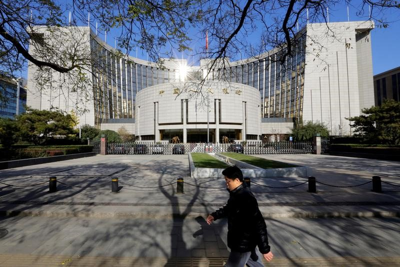 A man walks past the headquarters of the People's Bank of China (PBOC), in Beijing. Photo: Reuters/Jason Lee