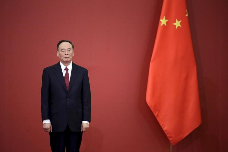China's Politburo Standing Committee member Wang Qishan, the head of China's anti-corruption watchdog, stands next to a Chinese flag, in Beijing, China, September 2, 2015. Photo: Reuters/Jason Lee