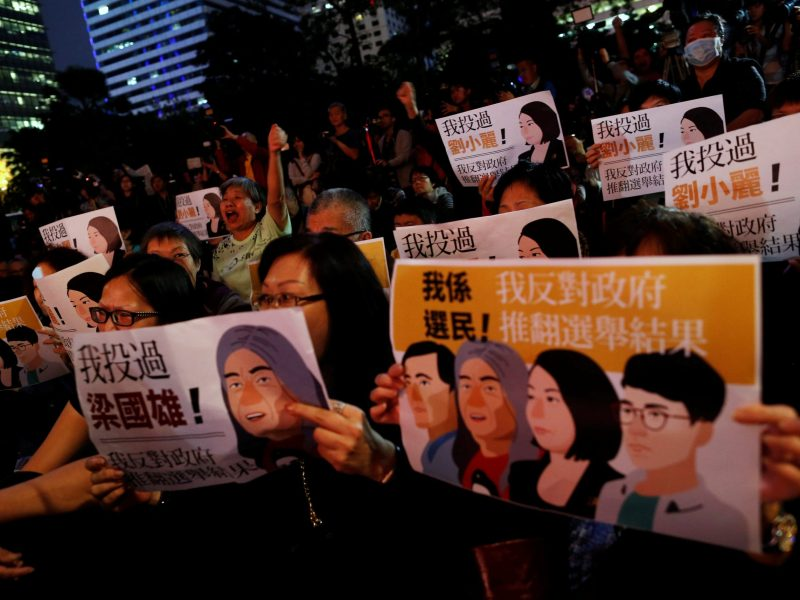 "Pro-democracy supporters take part in a rally against a government decision to commence separate legal proceedings against four legislators over oaths taken at a Legislative Council, in Hong Kong, China December 10, 2016. Poster on right reads ""I am a voter, I am against the government overthrowing the election results."" REUTERS/Tyrone Siu"