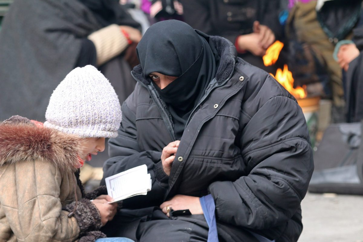 A woman sits with her child reading the Koran while waiting to be evacuated with others from a rebel-held sector of eastern Aleppo. Photo: Reuters/Abdalrhman Ismail