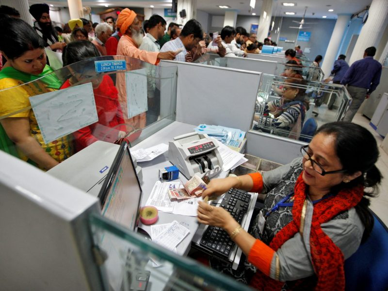 A cashier counts Indian banknotes as customers wait in queues inside a bank in Chandigarh in December 2016. Photo: Reuters/Ajay Verma