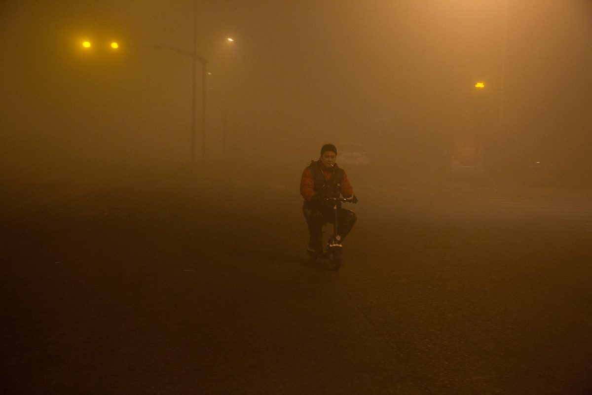 A man smokes on a very small bicycle in Beijing on December 22, 2016. Photo: Reuters / Stringer
