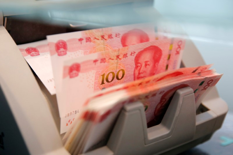 Chinese 100 yuan banknotes are seen in a counting machine while a clerk counts them at a branch of a commercial bank in Beijing, China, March 30, 2016. Photo: Reuters/Kim Kyung-Hoon