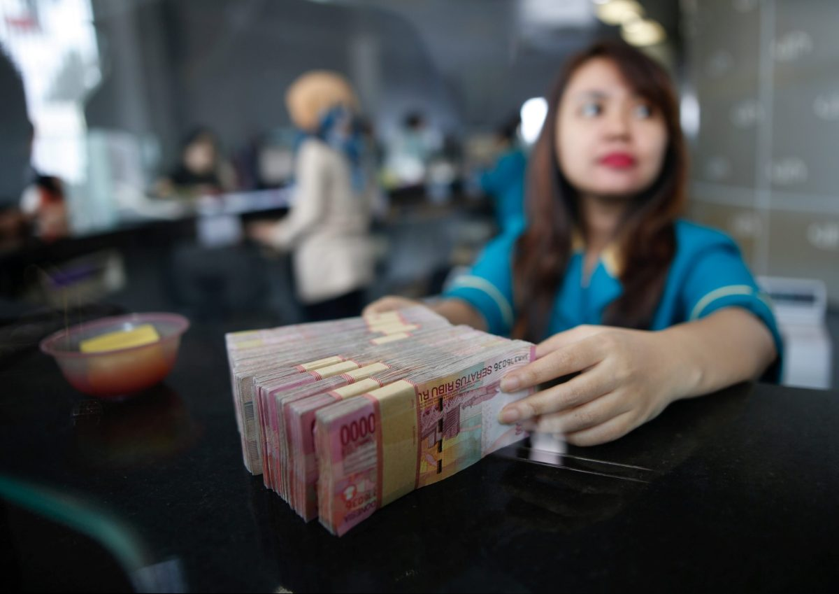 A teller at a money changer handles Indonesia rupiah bank notes in Jakarta, Indonesia. Photo: REUTERS/Darren Whiteside