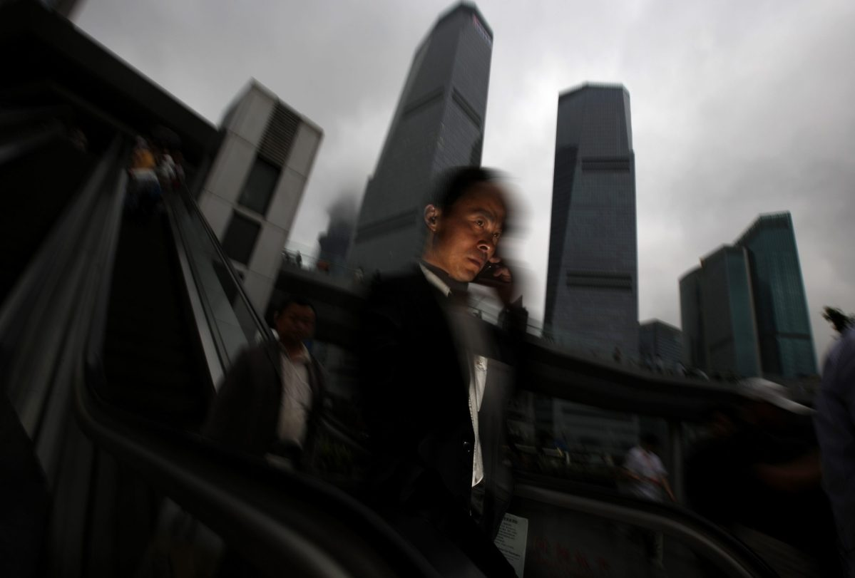 A businessman talks on his mobile phone as he walks in the financial area of Pudong in Shanghai. Photo: Reuters, Carlos Barria