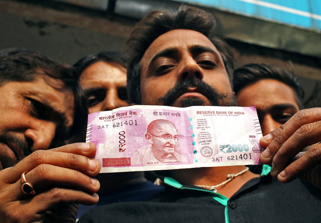 A man displays a new 2000 Indian rupee banknote after withdrawing from a bank in Jammu. REUTERS/Mukesh Gupta