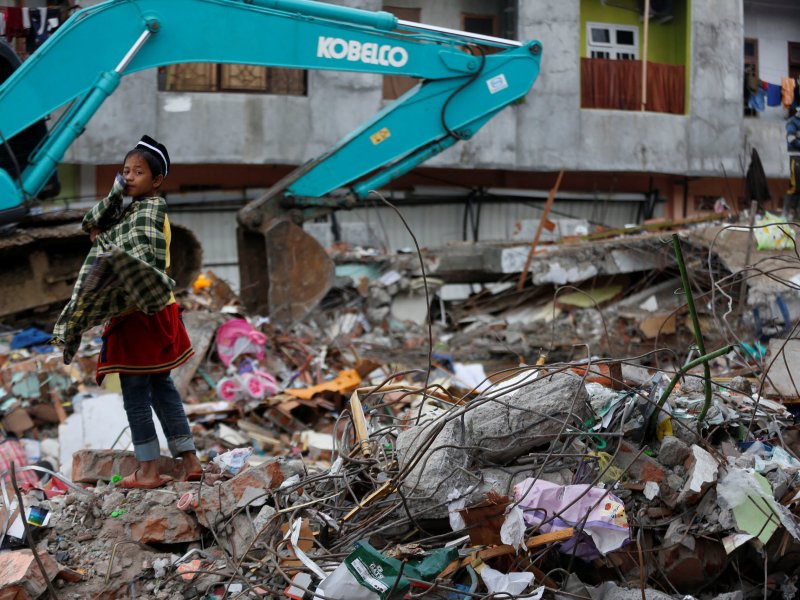 A boy stands on rubble from a collapsed building following this week's strong earthquake in Meureudu market, Pidie Jaya, Aceh province, Indonesia December 9, 2016. REUTERS/Darren Whiteside