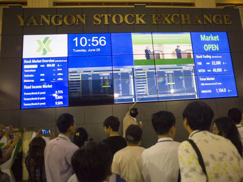 People monitor stock prices and the index displayed on a large video screen at the Yangon Stock Exchange in Yangon on June 28, 2016.  Photo: Ye Aung Thu/AFP Photo