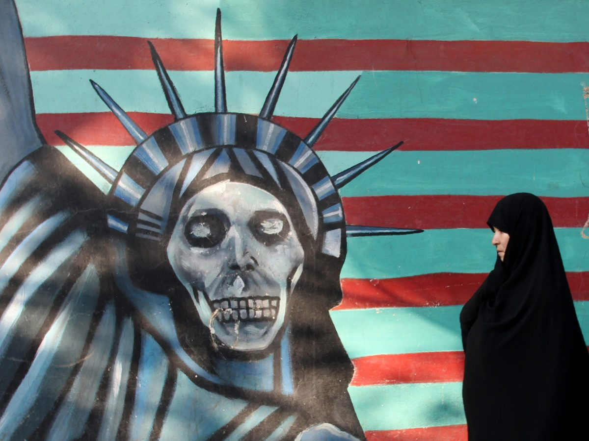 An Iranian woman walks past a mural on the wall of the former US embassy in the Iranian capital Tehran. Photo: AFP / ATTA KENARE